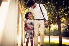 Talk about school. African American father and his daughter walking trough city park royalty free stock image