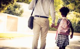 Back to school. African American father and his daughter walking trough park. From back royalty free stock photo