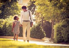 Day for school. African American father and his daughter walking trough park stock photos
