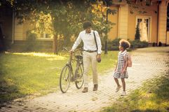 Day for work and school. African American father and his daughter walking trough park and talking royalty free stock photo