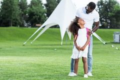 African american father hugging daughter with school bag. In park stock image