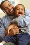 Father hugging and laughing with his son. African American Father hugging and laughing with his son Royalty Free Stock Images