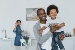 African american father hugging son and mother waving hand. At home royalty free stock photo