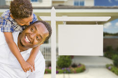 African American Father and Mixed Race Son In Front of Blank Real Estate Sign and House royalty free stock photography