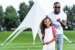 African american father pointing on camera to adorable daughter with school bag. In park royalty free stock photography