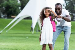 African american father pointing on camera to daughter with school bag. In park royalty free stock images