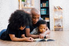 African American father reading a fairy tale fable story for kid. S at home. Happy family lying on the floor indoors royalty free stock image