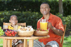 African American Father & Son Eating Food Outside. A happy, smiling African American father & son eating healthy food at a table outside, the father is Royalty Free Stock Photography