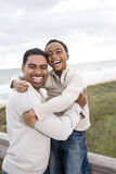 African-American father and son laughing at beach. Happy African-American father and ten year old son laughing at beach Royalty Free Stock Images