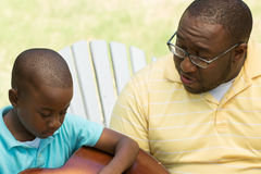 African American father and son playing the guitar. Royalty Free Stock Images