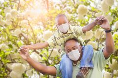 African American Father And Son Playing Outdoors Wearing Medical Face Mask