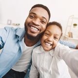 African-american father taking selfie with daughter at home. African-american father taking selfie with daughter, spending time together at home royalty free stock photos