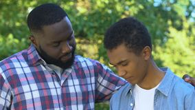 African-american father trying to comfort unhappy son, family support, trust