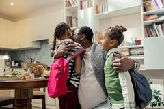 African-American father wearing glasses loving his daughters. Lovely daughters. Supporting African-American father wearing glasses loving his daughters stock photography