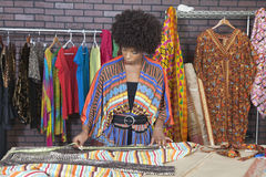African American female designer measuring cloth at design studio stock image