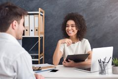 African-american female employer interviewing man in office stock images