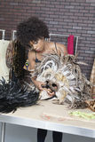 African American female fashion designer working on feather mask royalty free stock images