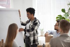 African American female give flipchart presentation for office w. African American millennial women speaker give flipchart presentation for colleagues, black stock image