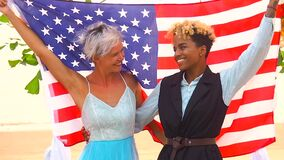 African american female groom in black suit and happy caucasian blonde bride loving together wrapped in america flag on
