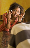 African-American female and male talk in kitchen. Upset African-American woman talking with a male family member in kitchen setting Royalty Free Stock Images