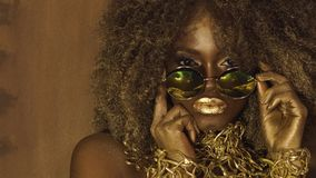African american female model in massive sunglasses with bright glitter makeup, glossy golden hairstyle and big red lips. Posing on the black studio background stock footage