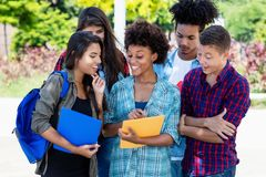 African american female student learning with group of latin and hispanic young adults stock photo