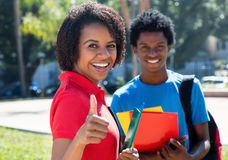 African american female student showing thumb with african male. Student outdoor on campus of university in summer Stock Images