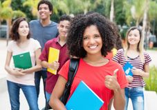 African american female student showing thumb with group of inte. Rnational students outdoor in the summer in the city outdoor in the summer in the city Royalty Free Stock Photography
