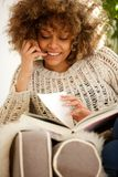 African american female student sitting at home and reading book. Portrait of african american female student sitting at home and reading book Stock Photography