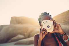 African american female taking pictures on the beach. Young woman using camera on sunny day stock photo