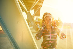 African american fit woman choosing music from an app for running at sunset Stock Photography