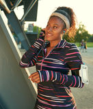 African american fit woman choosing music from an app for running at sunset Royalty Free Stock Photo