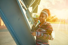African american fit woman choosing music from an app for running at sunset Stock Images