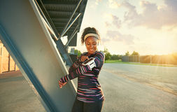 African american fit woman choosing music from an app for running at sunset Royalty Free Stock Images