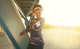 African american fit woman choosing music from an app for running at sunset Royalty Free Stock Image