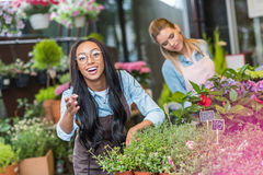African american florist in eyeglasses gesturing at camera while colleague working with plants behind Stock Photo