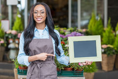 African american florist in eyeglasses holding blank sign and pointing at copy space Stock Photos