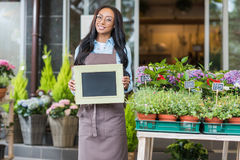 African american florist in eyeglasses holding blank sign and smiling at camera Royalty Free Stock Image