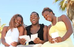 African American Friends Outdoors Laughing. Three African American Friends Outdoors Looking at Photographs and Laughing Royalty Free Stock Photo