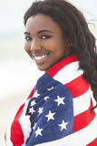 African American Girl in American Flag on Beach royalty free stock photo
