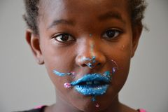 African American Girl with Bright Blue Frosting on Face Stock Photo