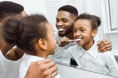African-american girl brushing teeth together with dad royalty free stock image