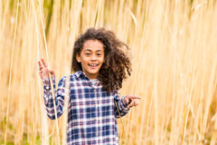 African american girl in checked shirt outdoors in field. Beautiful african american girl with curly hair in checked shirt outdoors in field stock photography