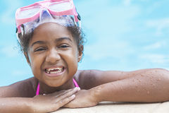 African American Girl Child In Swimming Pool. A cute happy young African American girl child relaxing on the side of a swimming pool smiling & wearing pink Stock Images