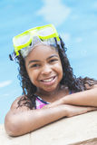 African American Girl Child In Swimming Pool. A cute happy young interracial African American girl child relaxing on the side of a swimming pool smiling & Stock Image