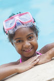 African American Girl Child Swimming Pool Wearing Goggles. A cute happy young African American girl child relaxing on the side of a swimming pool wearing pink Royalty Free Stock Photography