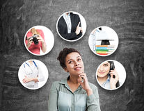 African American girl choosing career. African American women in a gray shirt is standing near a blackboard. There are five career choices around her Royalty Free Stock Images