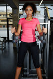 African american girl with curly afro hair training on weights press equipment at gym Royalty Free Stock Images