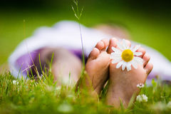 African american girl with daisy beteen toes. African american girl with feet facing the camera and daisy between toes Stock Photography