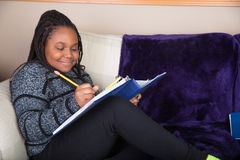 African American girl doing homework on the couch Stock Image